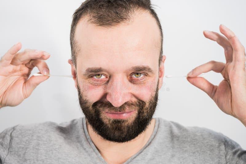 Mann, der Wachs vom Ohr unter Verwendung der Q-Spitze entfernt lizenzfreie stockfotos