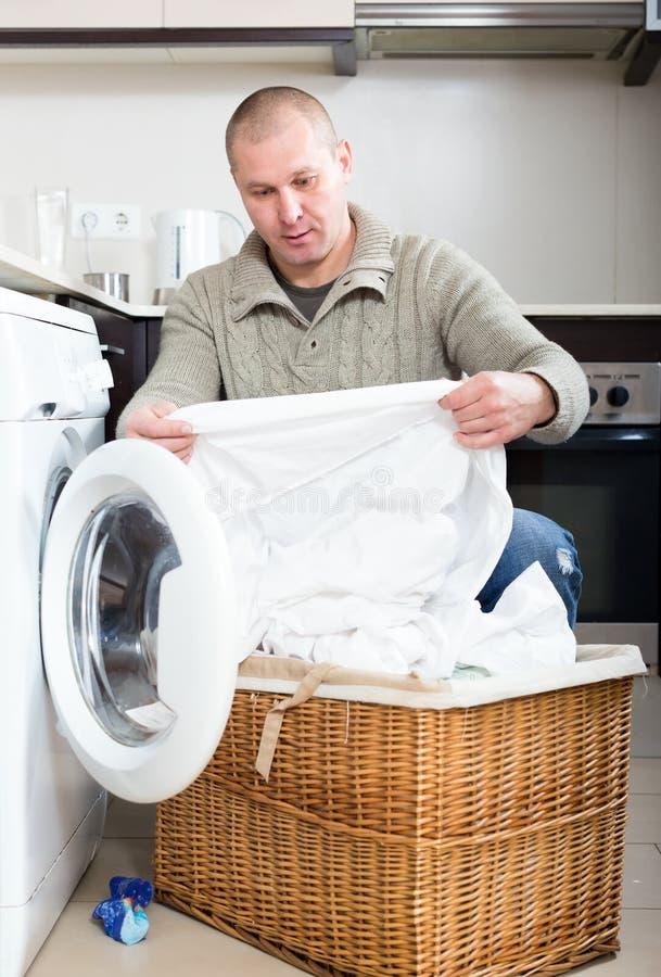 Mann, der Waschmaschine verwendet stockfotos