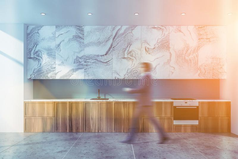 Mann, der in weiße Marmor- und blaue Küche geht lizenzfreies stockbild
