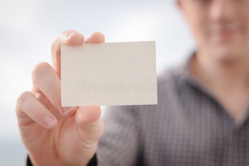 Mann, der weiße Visitenkarte auf Licht hält lizenzfreie stockbilder