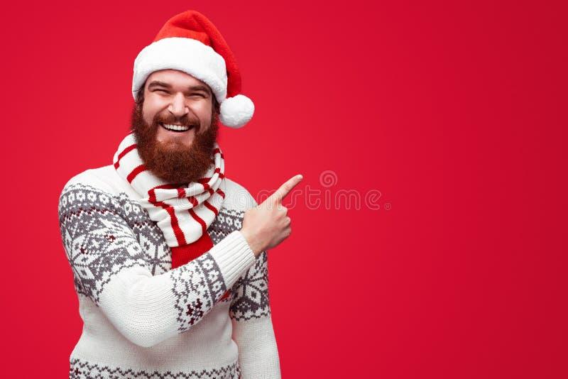 Mann in der Weihnachtskleidung weg zeigend auf das copyspace lokalisiert über Rot lizenzfreie stockfotografie