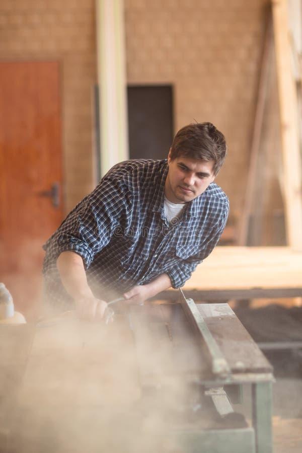 Mann in der Werkstatt, Zimmereiwerkstatt ordnend, Abwischen pneumatisch stockbild