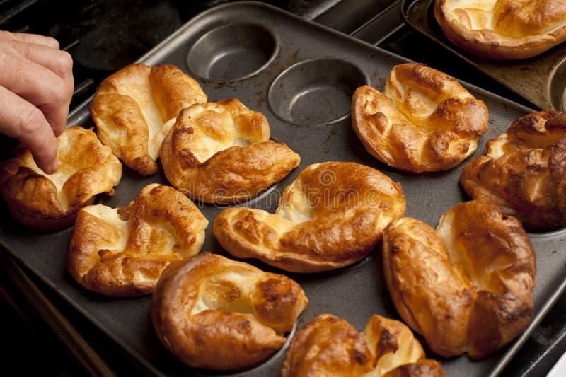 Mann, der Yorkshire-Puddings von einem Backblech entfernt stockfotografie