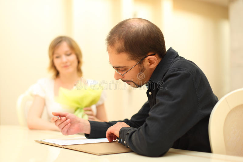 Mann, der Zeichen auf Hochzeitsdokumenten bildet lizenzfreies stockfoto