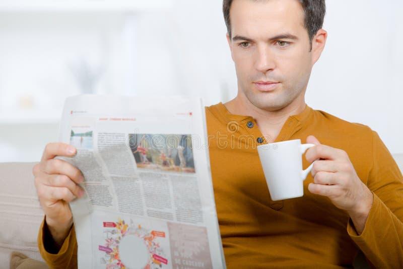 Mann, der Zeitung und Kaffee hält stockfotografie