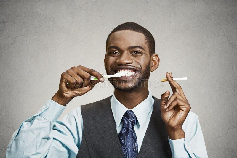 Mann, der Zigarette und Zahnbürste hält stockbild