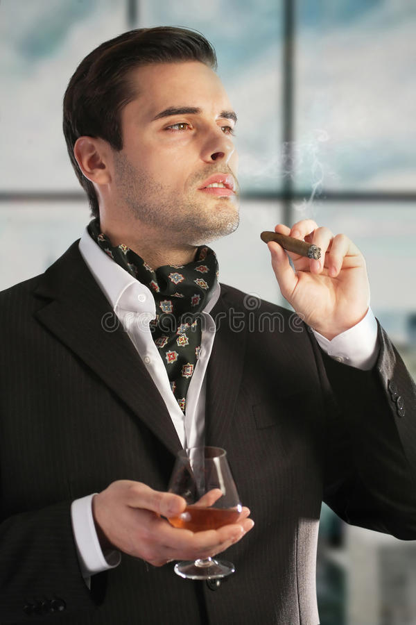 Mann, der Zigarre und Getränk genießt lizenzfreie stockfotografie