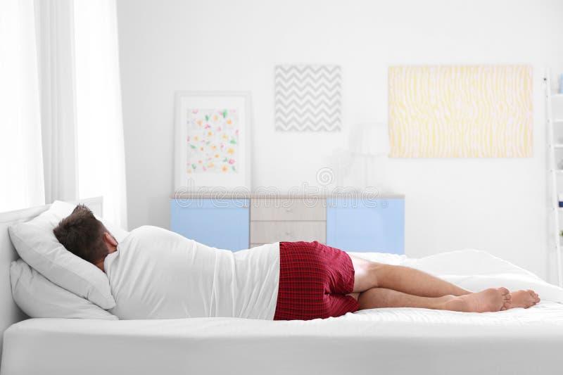 Mann, der zu Hause auf zwei Kissen schläft stockfotografie
