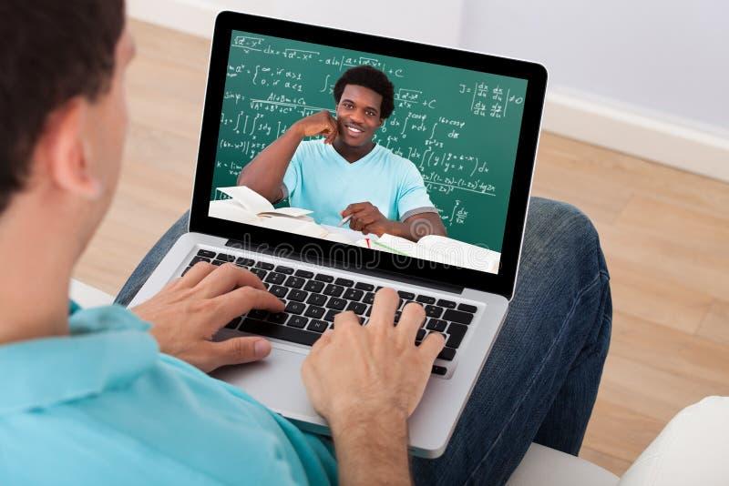 Mann, der zu Hause den Vortrag on-line-Mathe besucht stockbild
