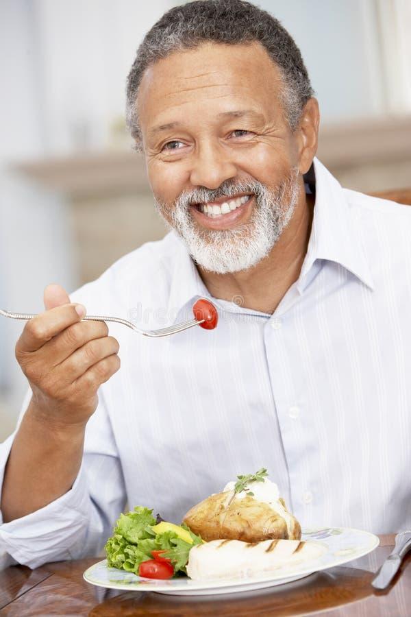 Mann, der zu Hause eine Mahlzeit genießt stockbilder