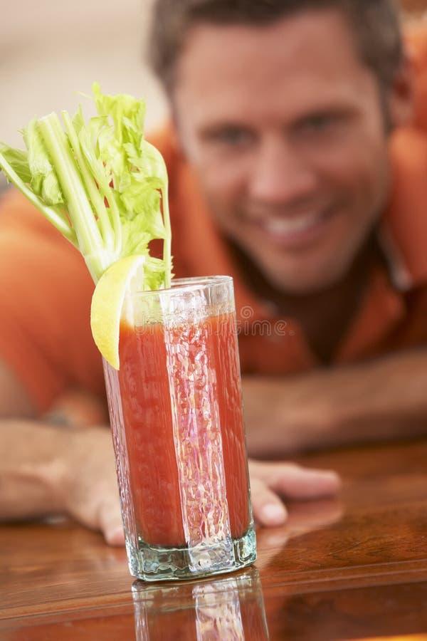 Mann, der zu Hause etwas trinkt lizenzfreies stockbild