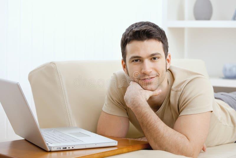 Mann, der zu Hause Laptop verwendet lizenzfreie stockfotografie