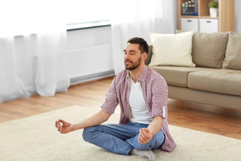 Mann, der zu Hause in der Lotoshaltung meditiert lizenzfreie stockfotos
