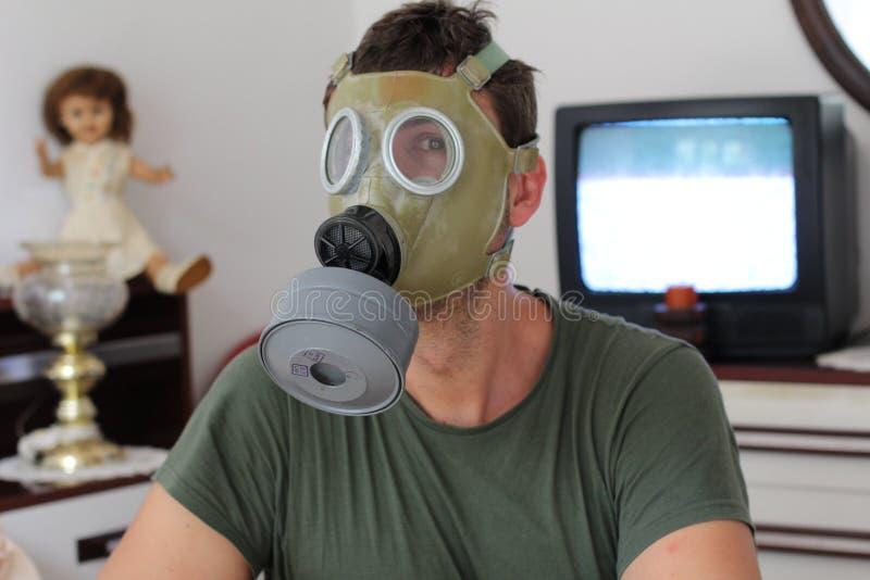 Mann, der zu Hause Retro- Gasmaske trägt stockbild
