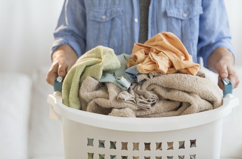Mann, der zu Hause Wäschekorb hält lizenzfreies stockfoto
