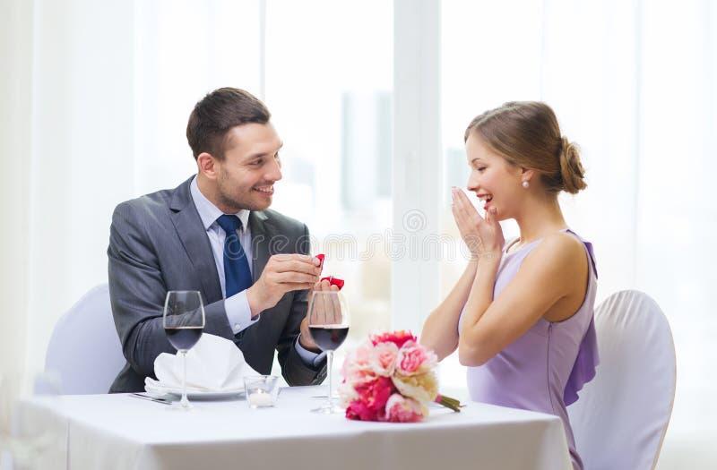 Mann, der zu seiner Freundin am Restaurant vorschlägt lizenzfreie stockfotos