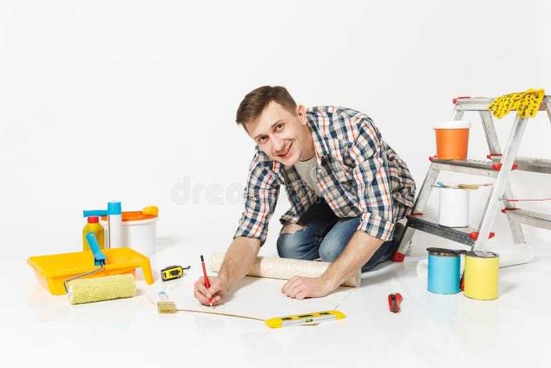 Mann in der zufälligen Kleidung, die auf Boden mit Rolle der Tapete, Bleistift, Instrumente für Erneuerungswohnungsraum sitzt lizenzfreie stockbilder