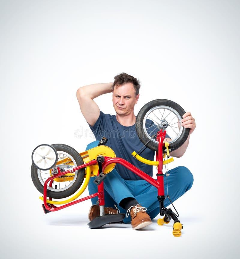 Mann in der zufälligen Kleidung, die ein Fahrrad der Kinder, die Rückseite seines Kopfes verkratzend repariert Auf hellgrauem Hin stockbilder
