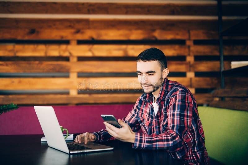 Mann in der zufälligen Kleidung, die im Laptop und im Handy arbeitet stockbilder