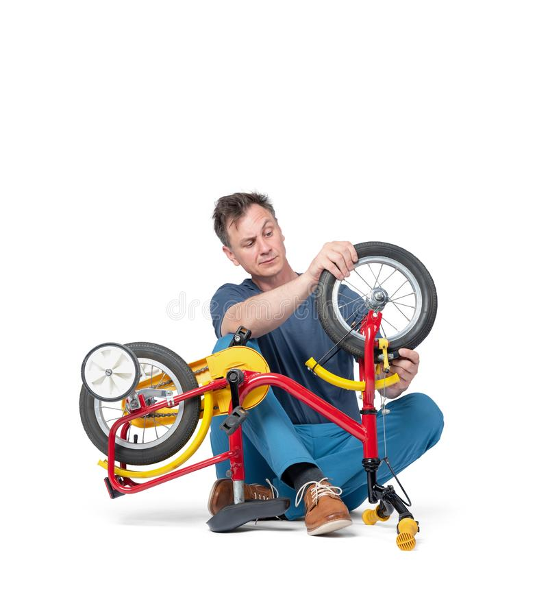 Mann in der zufälligen Kleidung repariert ein Fahrrad der Kinder und hält ein Rad, lokalisiert auf weißem Hintergrund lizenzfreie stockfotografie