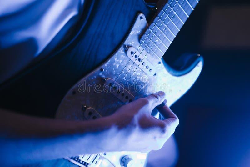 Mann, der zuhause Nahaufnahme der Gitarre auf dem Foto spielt stockbild