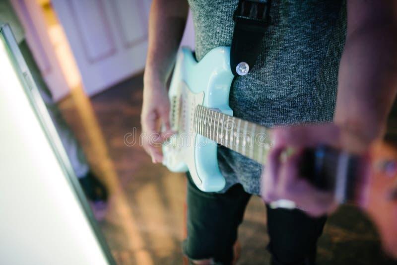Mann, der zuhause Nahaufnahme der Gitarre auf dem Foto spielt stockfotos