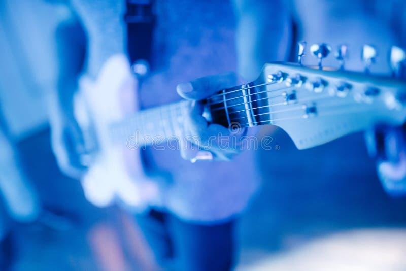 Mann, der zuhause Nahaufnahme der Gitarre auf dem Foto spielt lizenzfreie stockbilder