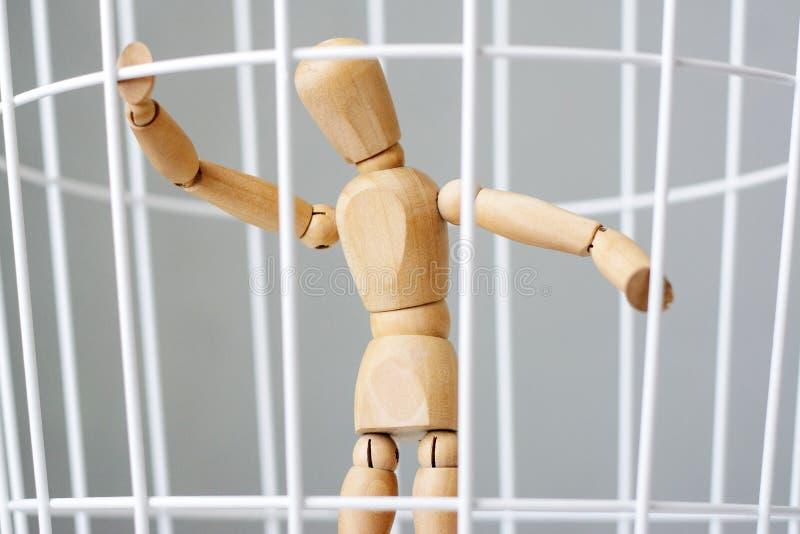 Mann des Holzes in einem Käfig lizenzfreie stockfotografie