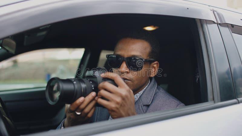 Mann des privaten Detektivs, der innerhalb des Autos sitzt und mit dslr Kamera fotografiert stockfoto