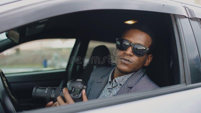 Mann des privaten Detektivs, der innerhalb des Autos sitzt und mit dslr Kamera fotografiert stockbild
