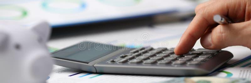 Mann drücken silbernen Schlüsseltaschenrechner ist von Hand ein stockfoto