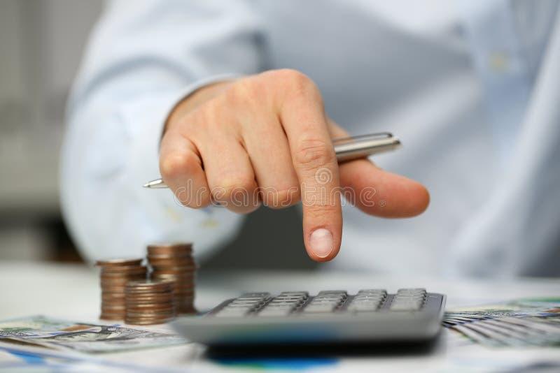 Mann drücken silbernen Schlüsseltaschenrechner liegt von Hand ein stockbilder