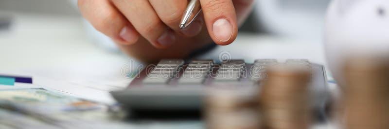 Mann drücken silbernen Schlüsseltaschenrechner liegt von Hand ein stockfoto