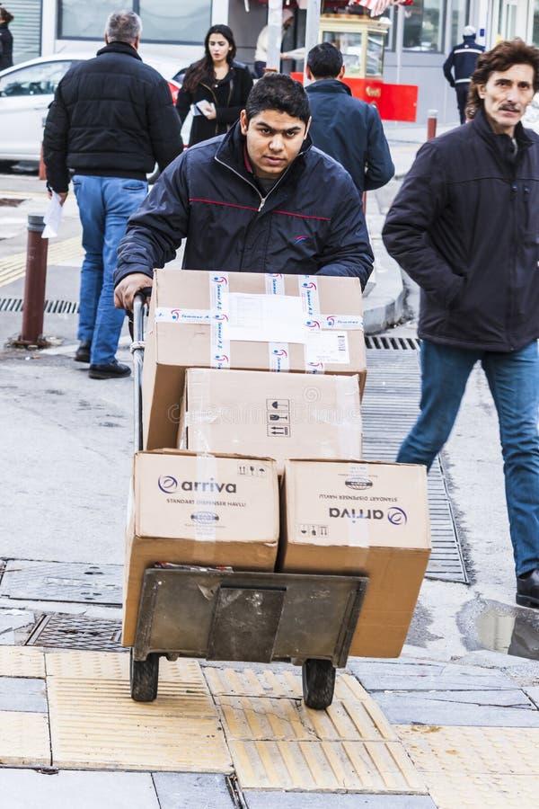 Mann drückt einen Warenkorb mit Pappschachteln lizenzfreie stockbilder