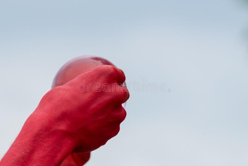Mann drückt roten Ball mit beiden Händen zusammen, um ihn zu brechen stockfoto