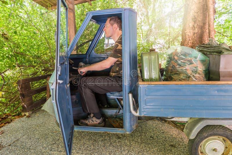 Mann in einem alten dreirädrigen Einsitzerfahrzeug, modellieren produziert zwischen 1984 und 1985 verwendet für die Gartenarbeit stockfotografie