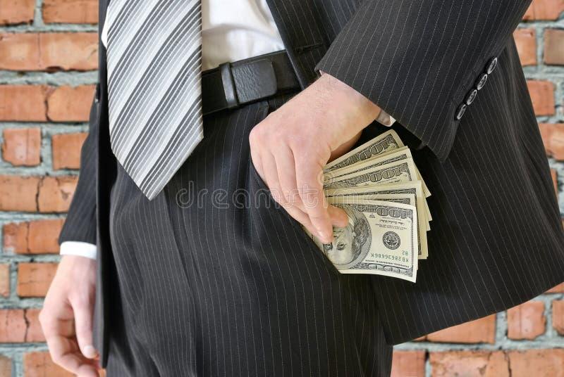 Mann in einem Anzug setzte Geld in Ihre Tasche ein lizenzfreies stockfoto