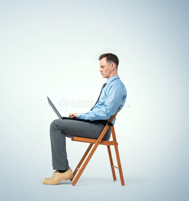 Mann in einem blauen Hemd mit einer Bindung sitzt auf einem Stuhl, der mit einem Laptop arbeitet lizenzfreies stockfoto
