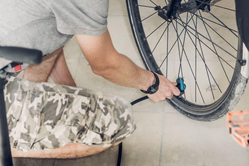 Mann in einem grauen T-Shirt und in den Tarnungskurzen hosen, die in geduckt sitzen stockbild