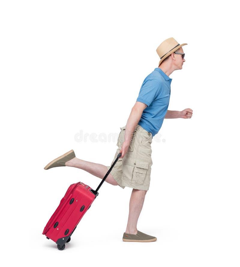 Mann in einem Hut, kurze Hosen, T-Shirt Läufe mit dem roten Koffer, lokalisiert auf weißem Hintergrund Spätes Passagierkonzept lizenzfreie stockbilder