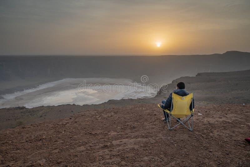 Mann in einem kampierenden Stuhl an einem vulcanic Krater während Sonnenaufgang Al Wahbah-Kraters in Saudi-Arabien lizenzfreie stockfotografie