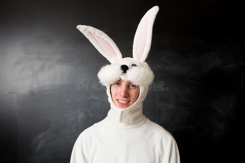 Mann in einem Kaninchenkostümlächeln stockbild