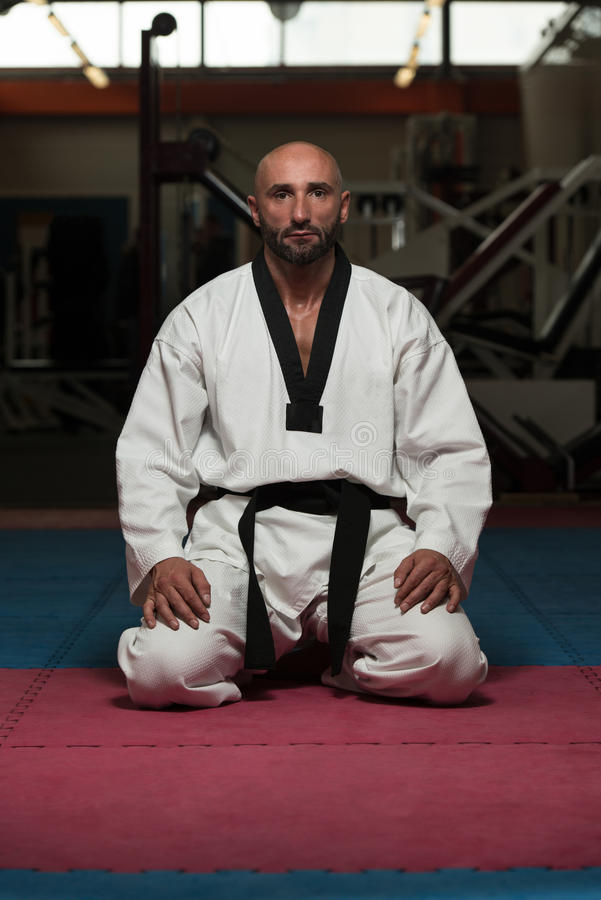 Mann in einem Kimono mit einem schwarzen Gürtel meditiert lizenzfreie stockbilder