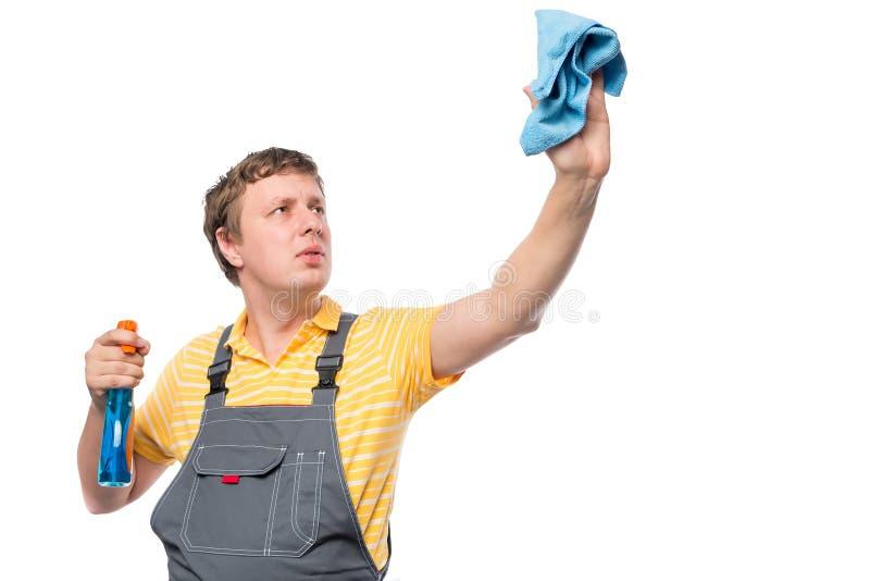 Mann in einem Overall hält eine Flasche mit Spray und Lappen stockfoto
