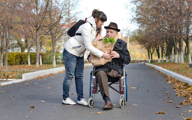 Mann in einem Rollstuhl, der bei den Lebensmittelgeschäften geholfen wird lizenzfreie stockfotografie