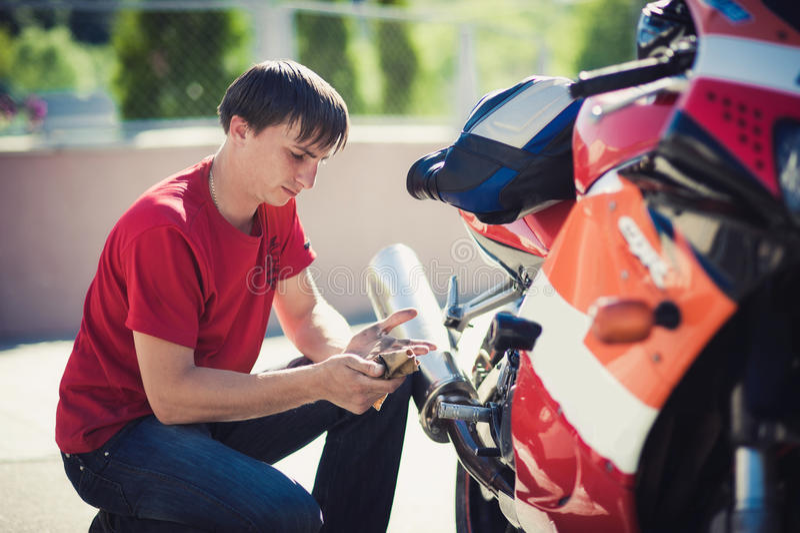 Mann in einem roten T-Shirt repariert ein Motorrad stockfoto