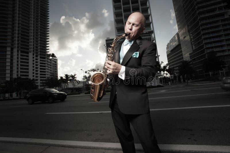 Mann in einem Smoking, der ein Saxophon spielt lizenzfreie stockfotografie