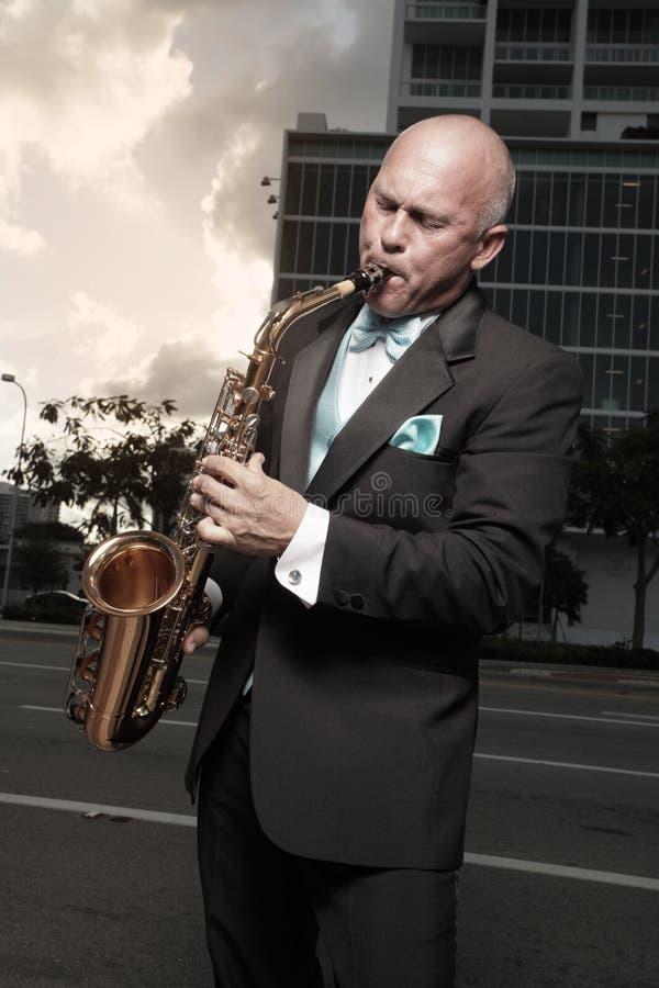 Mann in einem Smoking, der ein Saxophon spielt stockfotografie