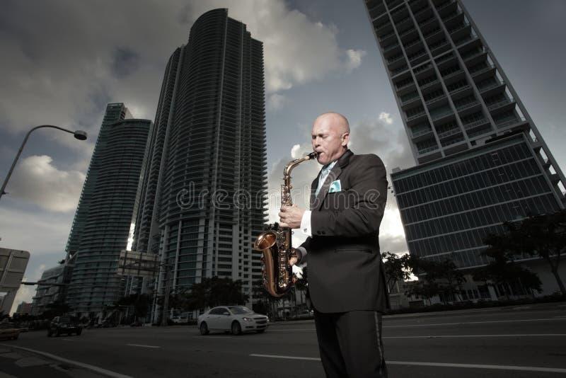 Mann in einem Smoking, der ein Saxophon spielt lizenzfreie stockbilder