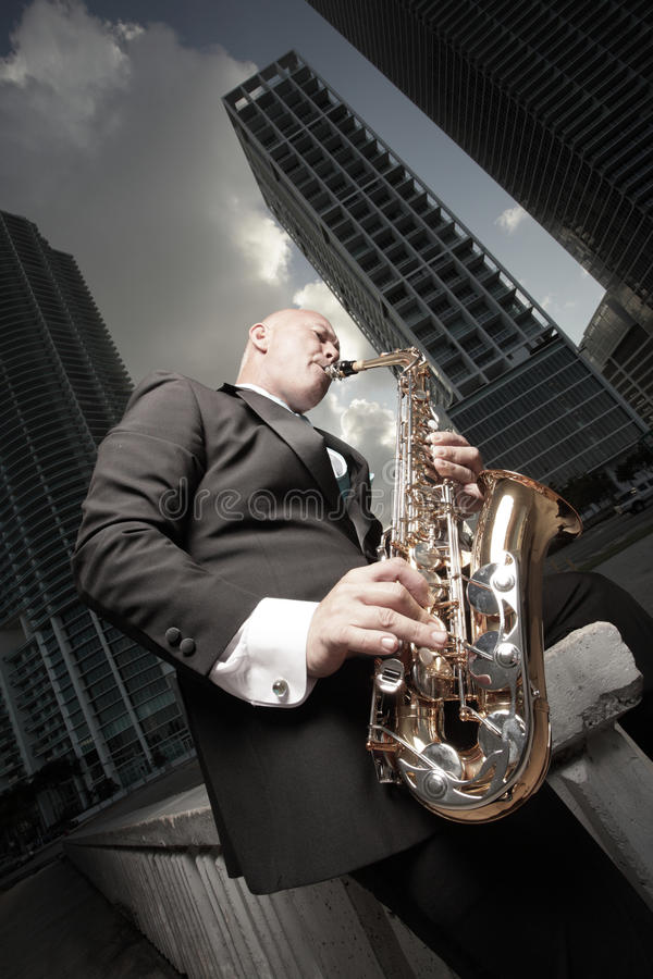 Mann in einem Smoking, der ein Saxophon spielt stockbild